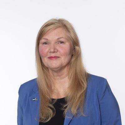 ett porträtt på en medelålders kvinna i blont hår som tittar in i kameran.