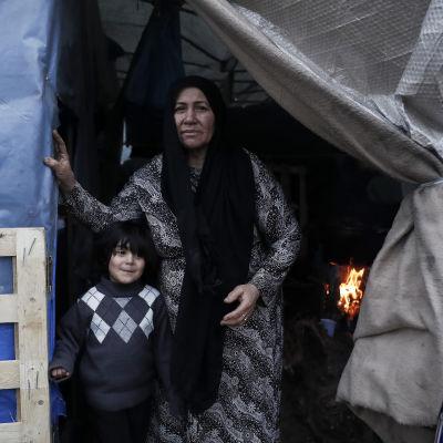 Nainen ja lapsi katsovat ulos telttarakennelman sisältä Morian-leirillä Kreikassa tammikuussa 2020.