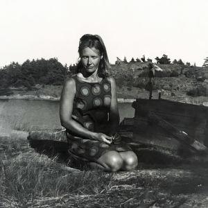 Nainen polvillaan kesämekossaan kalliolla saaristossa.