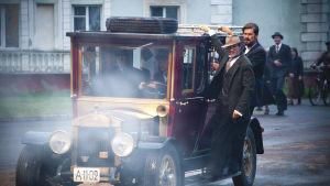 Strang och Jussi åker på genom staden hängande på en bil.