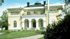 Aske herrgård, en gul byggnad i nyklassicistisk stil, ritad av Charles Bassi.