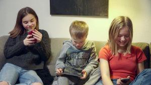 Kolme eri-ikäistä lasta istuvat sohjalla ja tuijottavat kännyköitä ja tabletteja.