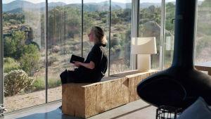 Nainen istuu asunnossa, joka on täynnä suurta lasi-ikkunaa.