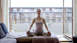 Nainen istuu sängyllä silmät kiinni lotusasennon kaltaisessa asennossa, takana näkyy parveke ja kerrostalo.