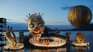 Rigoletto-oopperan suuret lavasteet järven rannalla. Lavasteina suuret puiset kädet, klovnin pää sekä ilmapallo.