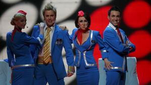 Ison-Britannian vuoden 2007 edustaja Scooch lavalla. Neljällä artistilla on siniset lentohenkilökuntamaiset asut yllään.