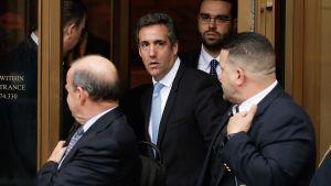 Trumps advokat Michael Cohen på väg ut från rättshuset omgiven av säkerhetspersonal