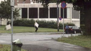 Kaksi miestä juoksee kadulla taulut mukanaan.