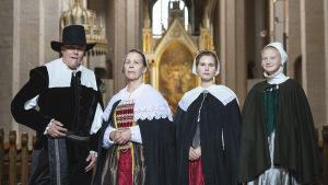 En man och tre kvinnor i gammaldags kläder står i Åbo domkyrka.