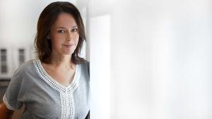 Kvinna med brunt hår och grå tröja med spetsbroderier lutar mot dörrpost.