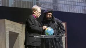 Äreksbiskop Kari Mäkinen och Mikael Agricola (Juhani Holma) tittar på en jordglob och funderar över framtiden för jorden.
