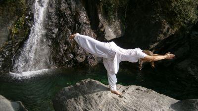 En kvinna som utför yoga på en klippa.