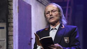 Etualalla Anna-Elina Lyytikäisen näyttelemä entinen portsari Vili lukee päiväkirjaa, takana Jukka Leistin hahmo istuu synkkänä.
