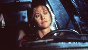 Närbild då Annie (Meg Ryan) sitter i en bil och funderar och ler.