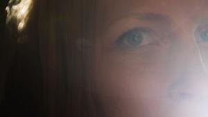 Närbild av en kvinnas ögon. Kvinnan kan inte identifieras från bilden trots att hon tittar på kameran på grund av den strikta beskärningen av bilden. Det starka ljuset från vänster skapar en disig atmosfär i bilden.