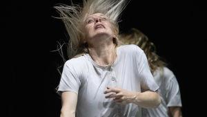 """Kvinna med ljust flygande hår på en säng på Nationalbalettens """"Jekyll & Hyde""""."""
