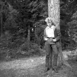 En ung Anders Wiklöf står lutad mot ett träd.