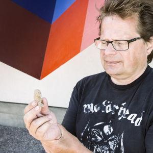 Vantaan Jokiniemen kaivausten johtaja, arkeologi Jan Fast pitää kädessään Jokiniemestä vuonna 2014 löydettyä savi-idolia