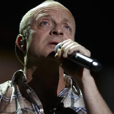 Jonas Gardell, närbild, tittar snett uppåt, håller i en mikrofon.
