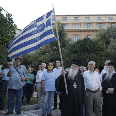 Grekisk-ortodoxa som håller i grekisk flagga demonstrerar i Aten.