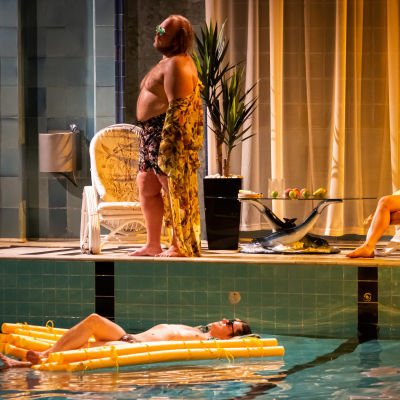 Tre personer i morgonrockar latar sig vid en vacker simbassäng.