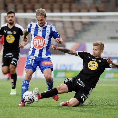 Petteri Pennanen försöker tackla bollen av Akseli Pelvas.