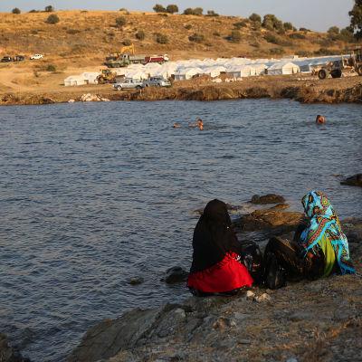 Kaksi turvapaikanhakija naista istuu meren rannalla Lesboksen saarella.