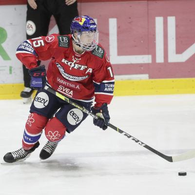 Anton Lundell i HIFK:s röda tröja med pucken på isen i en ligamatch.