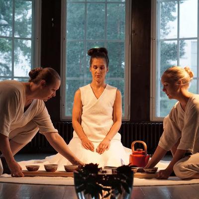 En kvinna i vit klänning sitter på golvet, framför henne står en tekanna och små koppar. Intill henne sitter två kvinnor i vitt på huk.