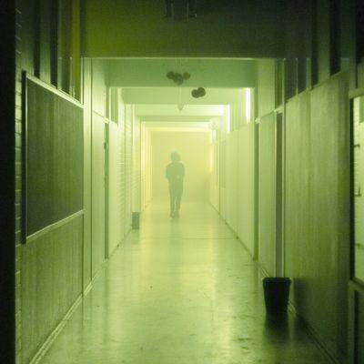 En disig och dunkelt upplyst skolkorridor. Längst borta i korridoren syns siluetten av en gående person.