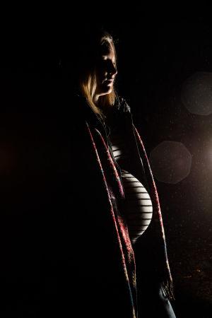 En gravid kvinna står på en grusväg i ett utomhusområde på natten. Kvinnans mörka profil tas från ficklampan som kommer bakom bilden. Den unga kvinnan kan inte identifieras på bilden.