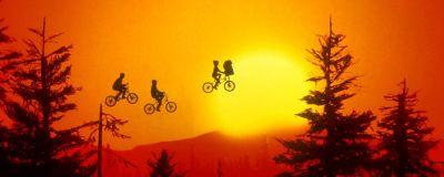 En rödtonad bild där man ovanom skogstopparna ser tre cyklister som flyger i luften.