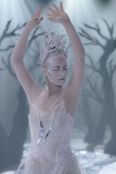 En kvinna med vitt smink och krona på huvudet.