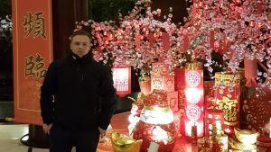 En man klädd i svart poserar framför en röd banderoll med kinesiska tecken. Mannen står brevid en ljusinstallation av kinesiska lampor och körsbärsträd