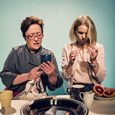 Väninnorna Cecilia (Carola Sarén) och Maria (Lina Ekblad). Cecilia vänder sig till Facebook för att försöka få tag i en elektriker..