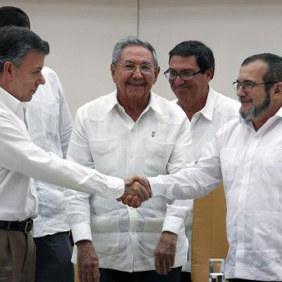 Colombias president santos och Farc-ledaren Londono skkar hand efter i överenskommelse i Kuba.