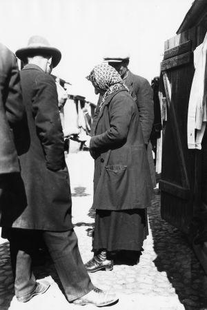Bild från det judiska Narinken på 1920-talet. Kvinna i duk omringad av män. Handelsplats.
