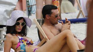 Jon Hamm och Jessica Pare ligger på stranden i tv-serien Mad Men.