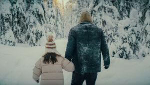 Far och dotter vandrar mot solen genom ett snötcäkt landskap.