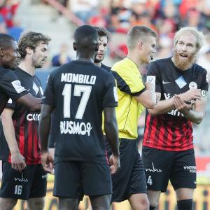 Svartklädda fotbollsspelare från PK-35 diskuterar vilt med domare.