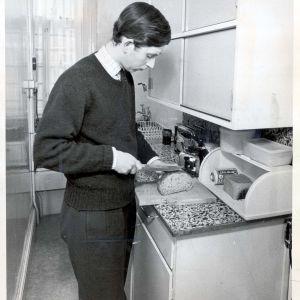 Prins Charles skär upp bröd i sin bostad på Trinity College, Cambridge 1969.