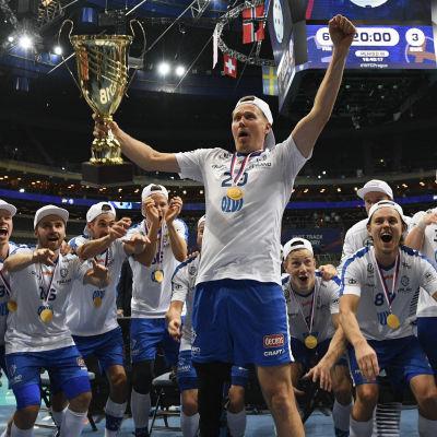 Mika Kohonen håller upp VM-pokalen och lagkamraterna gör vågen bakom honom.