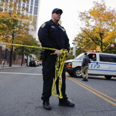 En polis avgränsar området vid brottsplatsen.