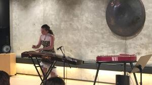 Barbora Xu står och spelar på sin kinesiska guzheng som påminner om en stor kantele.