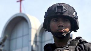 En indonesisk polis utanför en av de kyrkor i Surabaya som utsattes för attentat på söndagen.