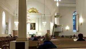 Fåtal kyrkobesökare i Kuopio domkyrka, bilden tagen inne i domkyrkan.
