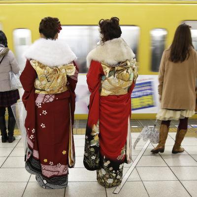 Kaksi kimonopukuista naista odottavat metrojunaa asemalaiturilla.