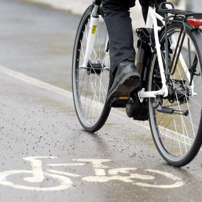 Mies ajaa sähköpyörällä pyörätiellä.