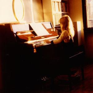 Nuori tyttö soittaa pianoa auringon iltasäteiden valossa.
