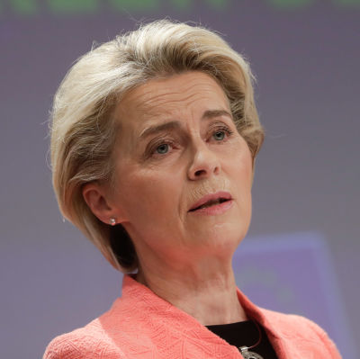 Ursula von der Leyen i rosa kavaj framför ett podium.